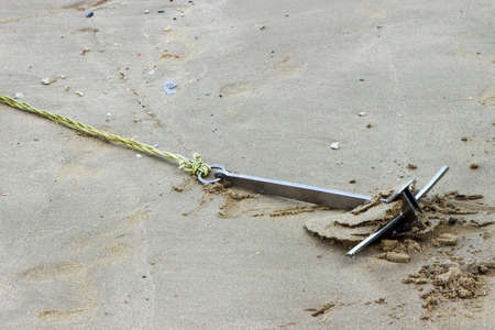 Metal anchor with a tied rope on the sand 免版税图像