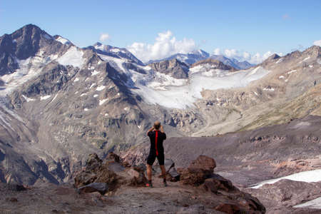 Side view of a male climber taking picture of snowy mountains on peak