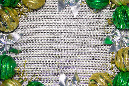 Christmas concept, New Year gifts. Copy space framed by decorations. Green and gold Christmas toys. 版權商用圖片