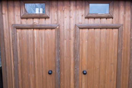 New Toilet and shower made of wood closeup. Garden plot. Glass small Windows. Two wooden doors. Country plot. Stok Fotoğraf