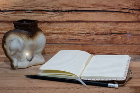 Open notebook with white pencil and candle on wooden background. Stok Fotoğraf