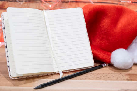 notebook,red Christmas hat and pencil on wooden table on background christmas garland.