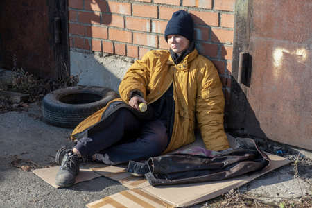 Homeless woman in a yellow old ragged jacket and blue hat is sitting on cardboard on the pavement and there is an old Apple Stock Photo