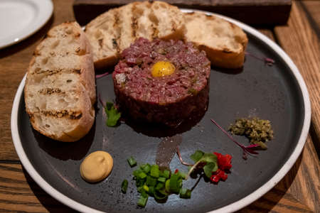 Beef tartare with pickled cucumber and fresh onion on dark marble background close-up.