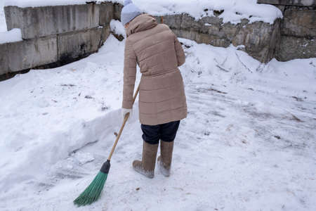 a woman in felt boots with a broom sweeps the snow on the street