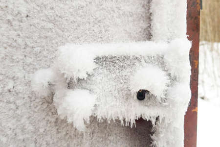 metal door and door handle and keyhole are covered with frost. severe frosts. door freezes. icy handle and lock covered with snowflakes
