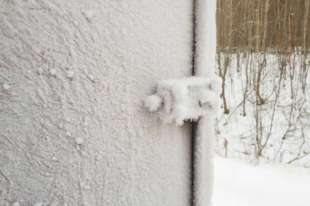 metal door and door handle and keyhole are covered with frost. severe frosts. door freezes. icy handle and lock covered with snowflakes. Imagens