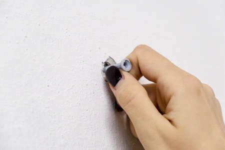 Female hand laying on the facade of a white plastic screw anchor dowel for the wall of the building.