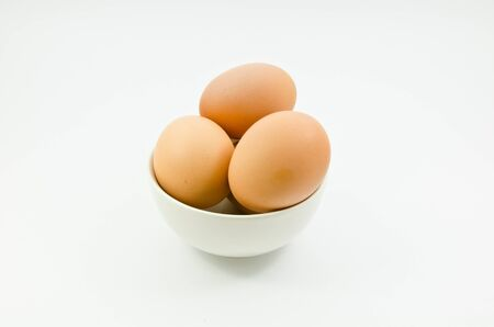 Three eggs in bowl on white background