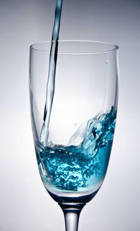 Blaues Wasser fallen in das Glas auf wei�em Hintergrund