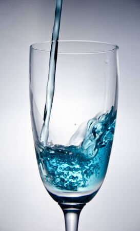 Blue water falling into the glass on white background