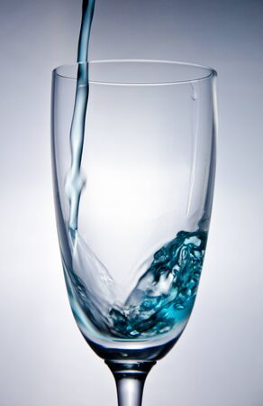 Blaues Wasser fallen in das Glas auf wei�em backgorund Lizenzfreie Bilder