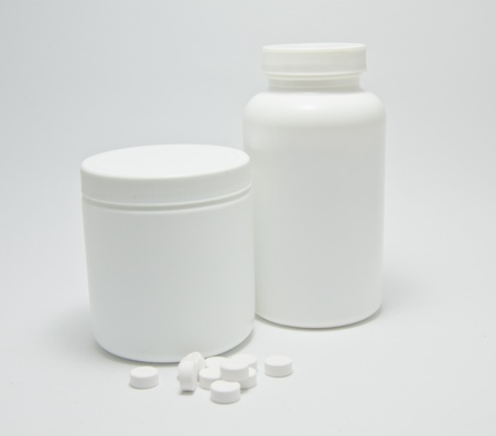 medicine bottle and pills on white background