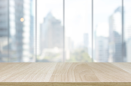 Wood table top and blur glass window wall building background - can used for display or montage your products. Stock Photo