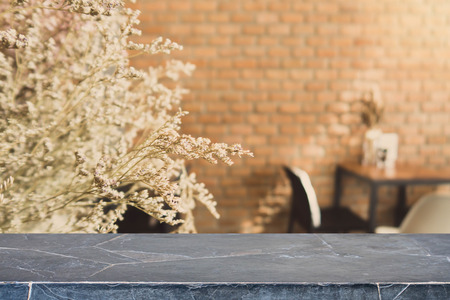 Stone table top and blurred bokeh cafe and coffee shop interior background with vintage filter - can used for display or montage your products.