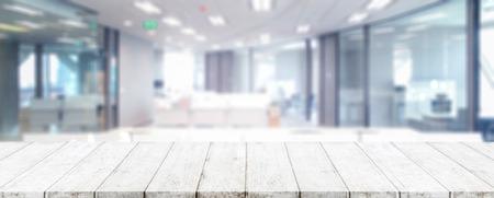 ウッドテーブルトップとぼやけたボケオフィスのインテリアスペースの背景 - ディスプレイやあなたの製品をモンタージュするために使用すること