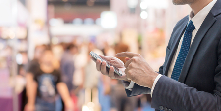 Businessman using smartphone Communicate at trade shows exhibition hall with full of people walking blurred background.