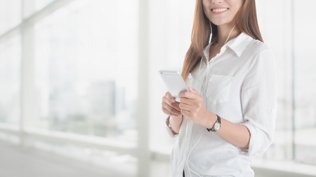 Beautiful young Asian girl using smart phone with earpiece in office space background and copy space.Concept of people using technology. Stock Photo