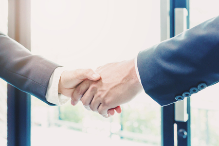 Businessman making handshake with a businesswoman - greeting and dealing concepts
