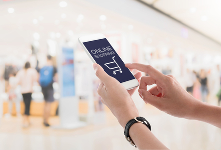 Woman hands holding and using smartphone with online shopping screen on blurred shopping mall interior background. Ecommerce concept.