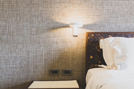 Beds in the hotel room with white pillows and wall lamps on the bedside. Stock Photo