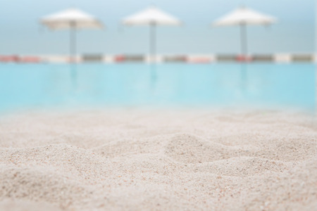 White sand on the beach with blurred swimming pool with benches and umbrella beach on sea background - can used for display or montage your products.