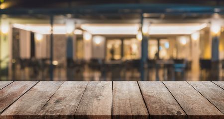 Wood table top and blurred night restaurant interior background - can used for display or montage your products.