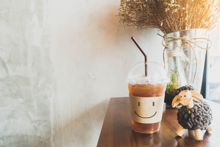 Ice coffee drink with smile face on wooden table in coffee shop cafe and copy space background with vintage filter