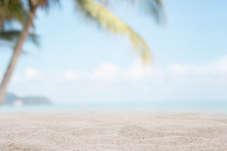 White sand on the beach with blurred sea and coconut tree background - can used for display or montage your products. Stock Photo