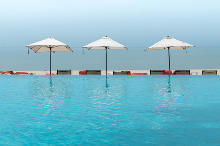 Luxurious hotel swimming pool with benches and umbrella beach on sea background.Concept of vacation and holidays.