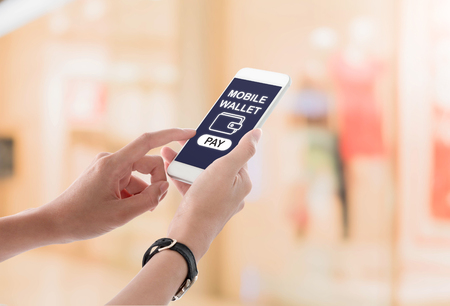 Woman hands holding and using smartphone with bill payment screen, wallet icon and pay button on blurred shopping mall interior background. Mobile payment concept. Stock Photo