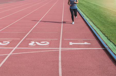 Female athletes are running into the finish line at number 1. In the running track of the stadium. Stock Photo