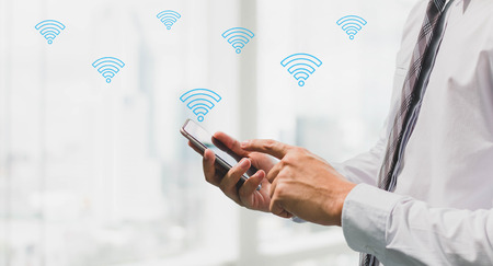 Businessman using smart phone with wifi icon on blurred interior office space background.