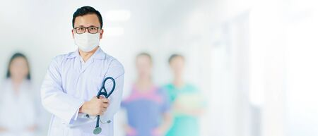 Portrait of Asian medical male Doctor wear a mask to prevent germs and standing in front of his blurred team staff in hospital background.Concept of effective work in hospitals.