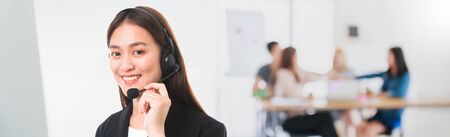 Asian Customer service operator woman with microphone headset working in call center contact office space banner background.Beautiful and smiling face.Telemarketing agent job concept.