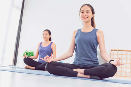 Asian beautiful woman and friends sitting and meditation in yoga lotus position in yoga classroom background.Concept of exercise for good health lifestyle.