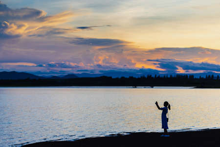 Silhouette woman standing at lake with mountain and sunset sky scenic landscape background with copy space. Stock fotó