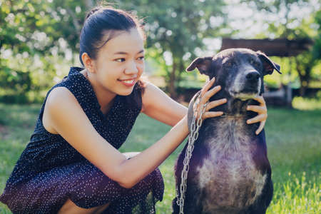 Asian young woman take dog to walk and play together in the backyard garden at home in the morning.Pet love lifestyle concept.