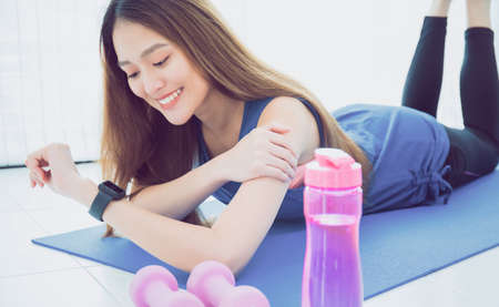 Asian woman resting and using smart watch after play yoga and exercise at home background with copy space. Concept of sport technology to checking health data.