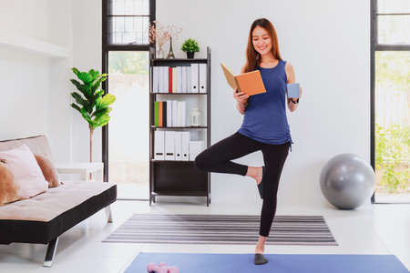 Beautiful asian fitness woman standing and reading book before exercise at living room  background. New normal lifestyle concept of lockdown, quarantine and social distancing. Stock fotó