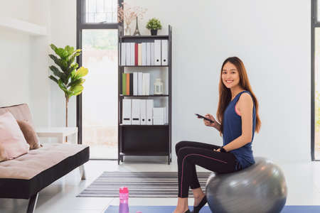 Beautiful asian fitness woman sitting on sport ball and using smartphone before exercise at living room  background. New normal lifestyle concept of lockdown, quarantine and social distancing.