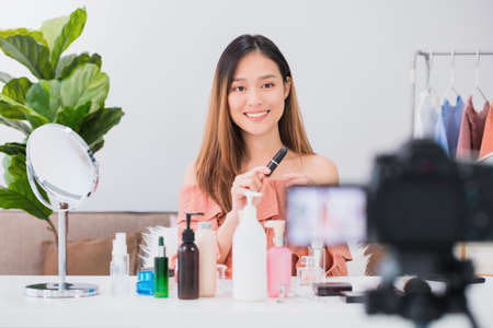Beautiful asian woman blogger is showing how to make up and use cosmetics. In front of the camera and recording vlog video live streaming at home.Skincare for healthy face concept.