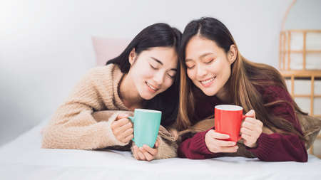 Young beautiful Asian women lesbian couple lover holding coffee cup in bed room at home with smiling face.Concept of LGBT sexuality with happy lifestyle together.