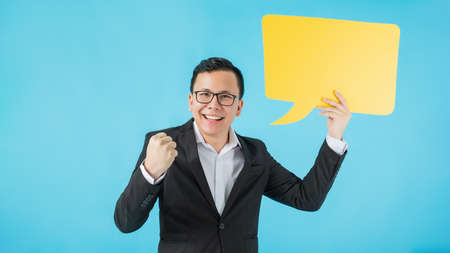 Asian happy business man smiling and holding yellow speech bubble isolated on on blue colour background with copy space.Concept of  success creative startup business.