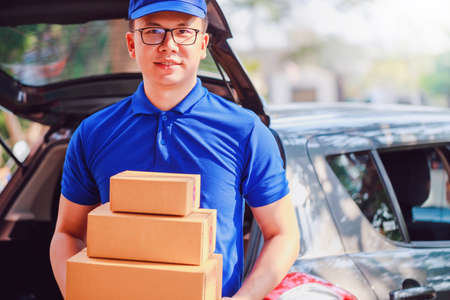 Asian delivery man wearing a blue shirt checking and carrying paper parcel boxes in the back of the delivery car with copy space.Concept of Postal delivery service.