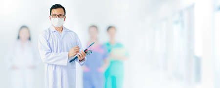 Portrait of Asian medical male Doctor wear a mask to prevent germs and standing in front of his blurred team staff in hospital background.Concept of effective work in hospital in situation of covid-19
