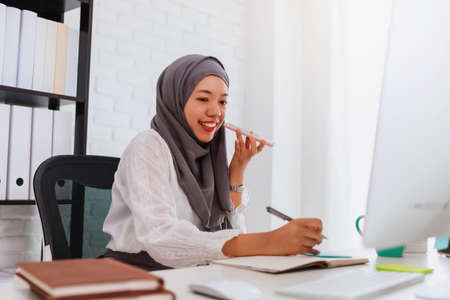 Asian muslim woman student or businesswoman waring hijab.Working from home with computer and smartphone.Concept of social distancing working alone at home in the epidemic situation of covid-19.
