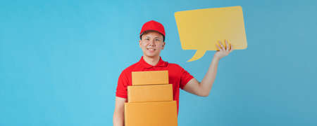 Asian happy delivery man wearing a red shirt while holding paper parcel boxes and yellow speech bubble isolated on on blue colour background with copy space.Concept of Postal delivery service. Stock fotó