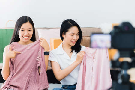 Two beautiful asian woman blogger showing and review clothing product.In front of the camera to recording vlog video live streaming at home.Business online influencer on social media concept. Stock fotó