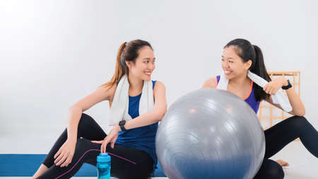 Asian women and friend talking together and resting after play yoga and exercise at home background with copy space.Exercise for Lose weight, increase flexibility And tighten the shape.